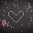 Heart shape made with candy on rubber black background — Stock Photo