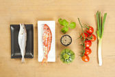 Fish preparation ingredients on wooden background — Stock Photo