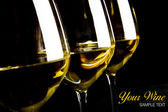Three glasses of white wine on black background — Stock Photo
