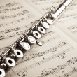 Stock Photo: Silver flute on ancient music score background