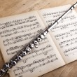 Silver flute on an ancient music score background - Stock Photo