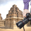 Photographer's hand holding professional digital camera on temple - Stock Photo