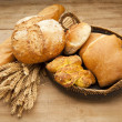 Assortment of fresh baked bread on wood table - Stock Photo