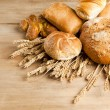 Assortment of fresh baked bread on wood table — Stock Photo #23098522