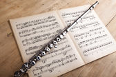 Silver flute on an ancient music score background — Stock Photo