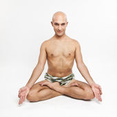 Young man practicing yoga on white background, meditating in lot — Stock Photo