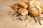 Assortment of fresh baked bread on wood table — Stok fotoğraf