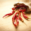 Red hot dry chili peppers over wooden background — Stock Photo