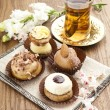 Different sort of beautiful pastry, small colorful sweet cakes with tea — Stockfoto