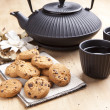 Beautiful teapot with chocolate biscuits on wooden table, delicious breakfast — Stock Photo
