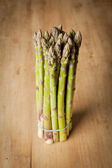 Bunch of fresh green asparagus on wooden background — Stock Photo