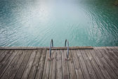 Old wooden pier on blue lake water — Stock Photo
