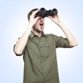 Young man looking through binoculars, surprise face expression — Stock Photo