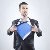 Young businessman acting like a super hero and tearing his shirt off — Stock Photo