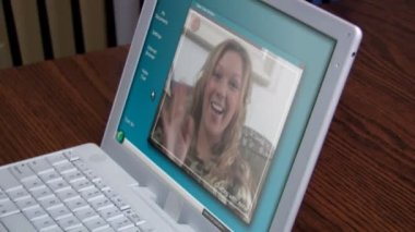 A woman video chats on her laptop at home.