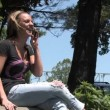 Royalty-Free Stock Vectorielle: A young woman talks on her cellphone outside in the park