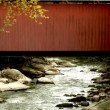 A red covered bridge over a flowing stream — Stockvideo