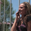 Royalty-Free Stock Векторное изображение: A young woman talks on her cellphone outside in the park