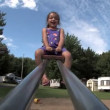 A young girl laughs on the see-saw — Stock Video