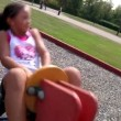 Stock Video: A young girl plays at the playground.