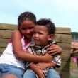 A brother and sister hug on a swing — Stockvideo