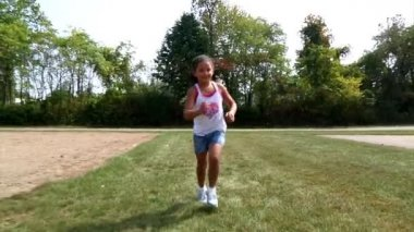 A young girl runs towards the camera. — Stock Video #13575196