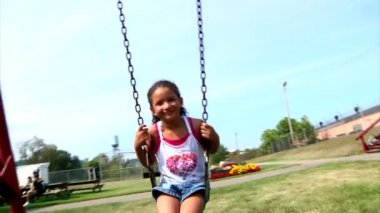 A young girl swings on a swing set — Stock Video #13575253