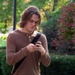 Stock Video: Students texting while walking on campus