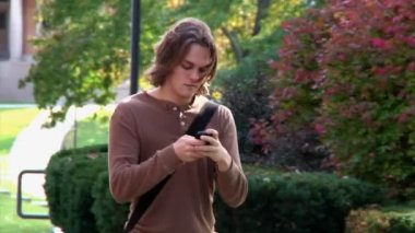 Students texting while walking on campus — Stock Video