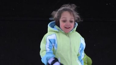 A little girl runs towards the camera in the snow. — Stockvideo