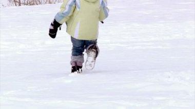 Uma menina foge da câmera na neve. câmera lenta. — Vídeo stock