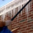 Breaking off dangerous hanging icicles from the roof. — Stock Video
