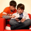 Stock Video: Two young boys play handheld video game.