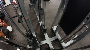 Lifting weights in a gym. Fisheye lens. — Vídeo de stock