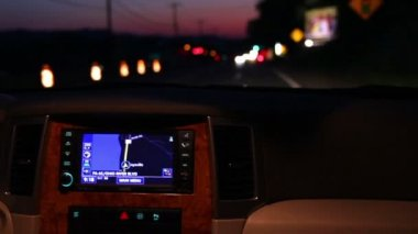 A man adjusts his in-dash GPS during a night drive. — Stockvideo