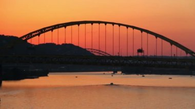 Traffic passes over the Fort Pitt Bridge during dusk in Pittsburgh, PA as pleasure boats travel underneath.