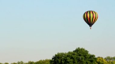 A hot air balloon gently glides through the air on a summer evening. — Stock Video