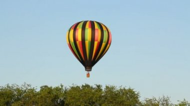A hot air balloon gently glides through the air on a summer evening.