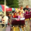 Kids riding a roller coaster at a carnival. — Stock Video #14566717