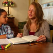 A young girl gets help with her homework. — Stockvideo