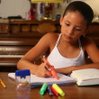 Stock Video: A young girl does her homework by herself in the dining room.