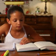 A young girl does her homework by herself in the dining room. — Stock video