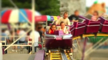 Kids riding a roller coaster at a carnival. — Stock Video