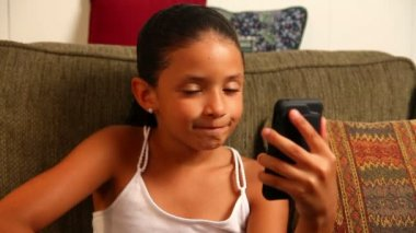 A young girl video chats on her mobile smartphone.