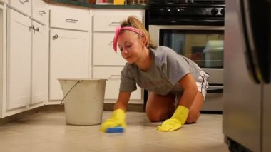 A young woman scrubs her kitchen floor. — Stock Video
