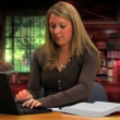 A college-aged girl does homework in the library with a laptop. — Stock video