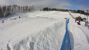 Riders slide down a snow tubing hill.