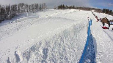 Jezdci sjíždět kopce sněhu trubky. — Stock video