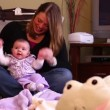 Stock Video: A mother plays with her new born daughter in her home.