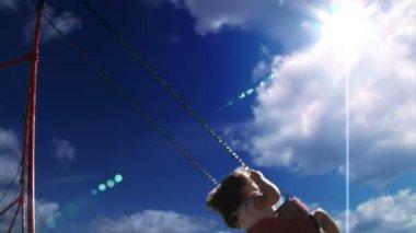Een jong meisje schommels op een schommel instellen in een speeltuin — Stockvideo